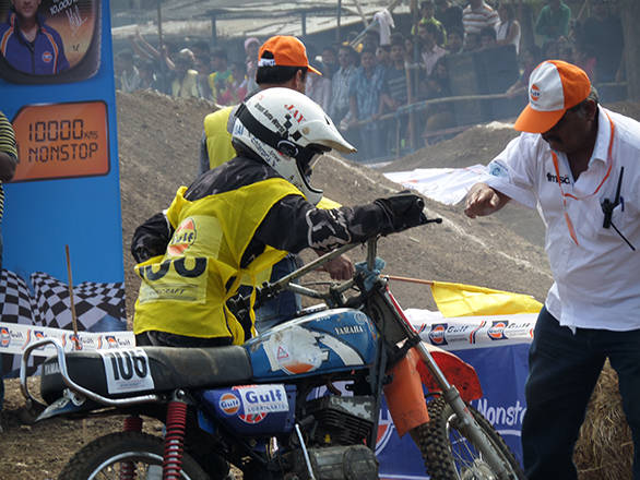 Nishi Shukla picking up her bike after taking a fall on the second lap