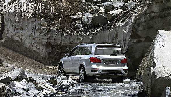 The GL inches across a dicey river crossing with precariously perched boulders just waiting to collapse onto the road