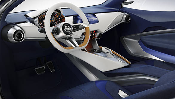 The interior uses a darker, deeper blue, with high contrasting ivory and orange colours matching the exterior to give a sense of unity to the car.