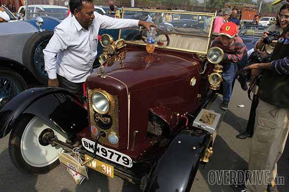 Fali Dhondy's Rover 8 being refueled. Learners car complete with two steering wheels and set of pedals. A war model amphibian vehicle. A 1936 Rolls-Royce Phantom III dominating the streets of Delhi