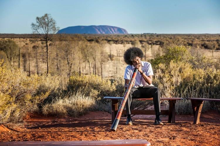 An indigenous Australian playing the wind instrument didgeridoo. In the backdrop is the Ayers Rock