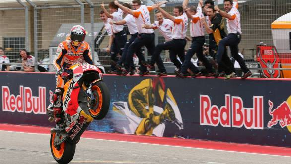 Marc Marquez celebrates his fourth consecutive victory at the Circuit of the Americas, as his Honda team cheers from the pit wall