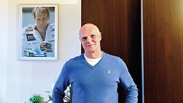 Georg Bellof in his home in Giessen, with a photo of his brother Stefan hanging behind him