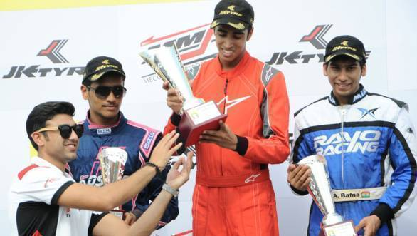 Ricky Donison accepts the trophy for first place in the Senior Max class, as Ameya Bafna and Nayan Chatterjee who finished second and third look on