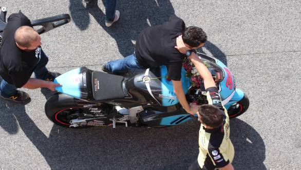 Mechanics wheel Luis Salom's motorcycle back into the garage after the MotoGP paddock bid the fallen rider a tearful goodbye
