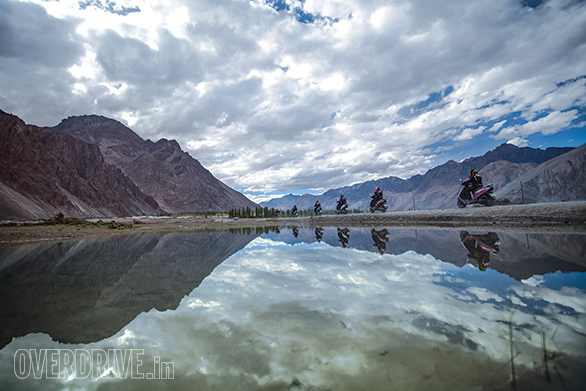 The rare appearance of lush green and flowing water marks the lush Nubra Valley plain through which the Shyok River flows with great urgency. Here the girls of the TVS Himalayan Highs Season 2 ride back to the main road after meeting the Bactrian camels of Hunder