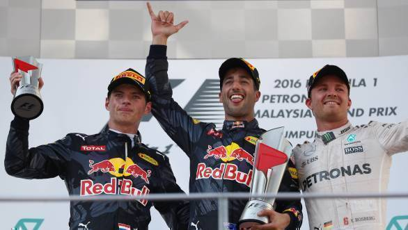 Daniel Ricciardo stands on the podium after winning the 2016 Malaysian GP, flanked by Red Bull Racing team-mate Max Verstappen and Mercedes driver Nico Rosberg - width=