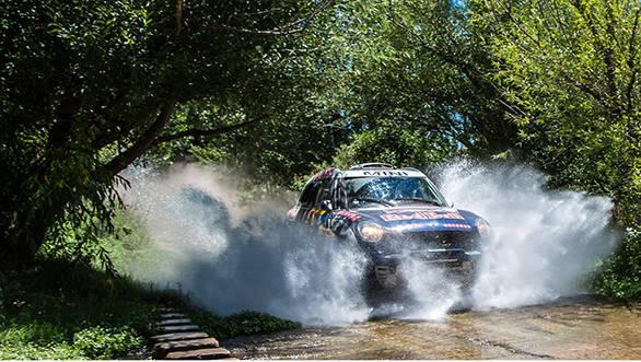 Nasser Al-Attiyah splashing through the rain soaked final stage